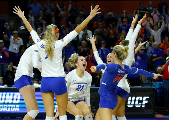 Florida players celebrate after winning in straight sets during the second round of the 2019 Division 1 Women's Volleyball Championship match against UCF at the Exactech Arena.