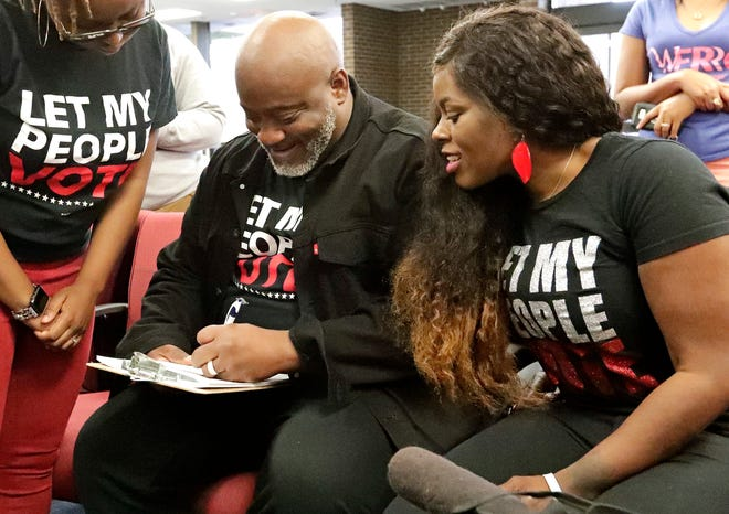 In this Jan. 8, 2019 photo, former felon Desmond Meade and president of the Florida Rights Restoration Coalition, left, fills out a voter registration form as his wife Sheena looks on at the Supervisor of Elections office in Orlando.