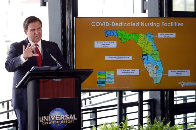 In this June 3 photo, Gov. Ron DeSantis speaks at a news conference at Universal Studios in Orlando as the theme park reopened.