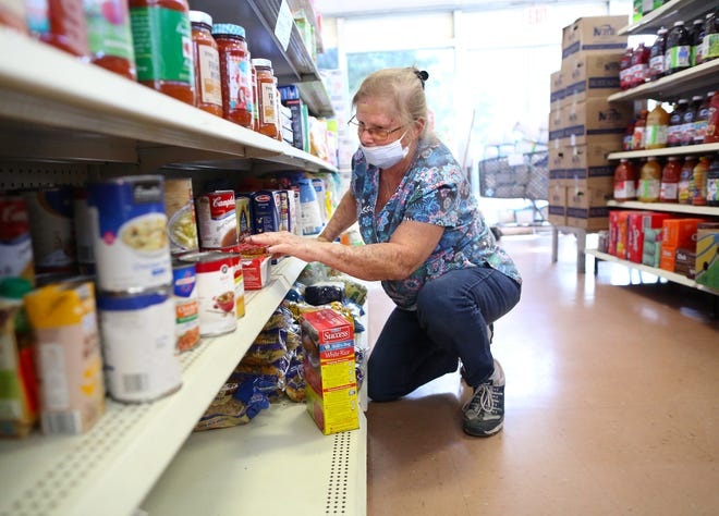 Kathy Hague, who works at Bread of the Mighty Food Bank, organizes food items on the shelves Wednesday. September is Hunger Action Month.