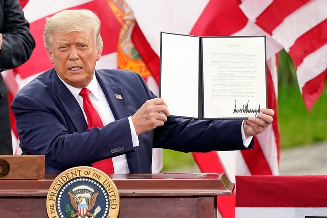 President Donald Trump holds a signed memorandum to expand the offshore drilling moratorium to Florida's Atlantic coast, Georgia and South Carolina after speaking at the Jupiter Inlet Lighthouse and Museum on Tuesday.