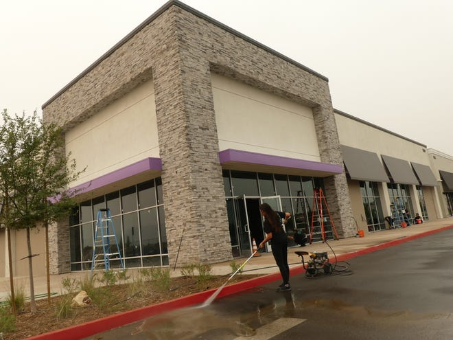 Shay Gaines, owner of Down and Dirty Cleaning Company, and her crew clean the outside of the newly constructed building that will soon house Planet Fitness at the new Mojave Plaza located in Hesperia.