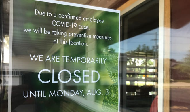 A sign on a business' window shows it closed temporarily due to COVID-19.