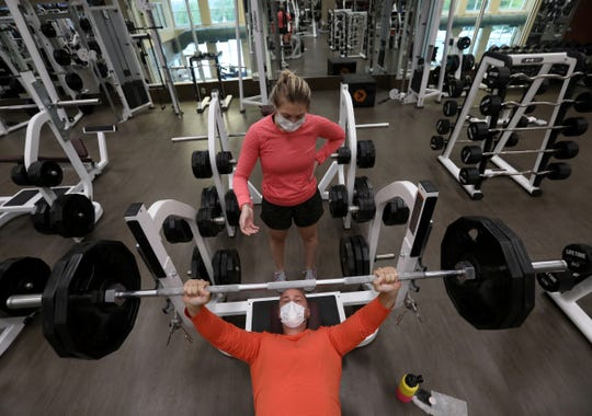 Danielle Champlin, 29, spots her fiance, Joshua Marvin, 30, on Wednesday at the Lifetime Fitness in Rochester Hills. This was the first day that fitness centers and gyms in lower Michigan opened up at 25% capacity since the coronavirus pandemic hit. Lifetime Fitness has many hand sanitizer stations, signs about wearing masks while social distancing and requires people to take a temperature scan at the front desk before heading in to work out.