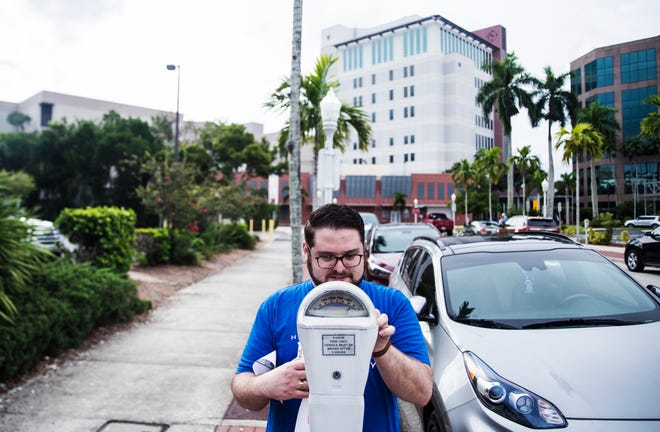 Jeffrey Haut, an attorney in the Fort Myers offices of the law firm Hahn Loeser pays a random parking meter in an act of kindness in downtown Fort Myers on Wednesday, September 9, 2020. The firm, which has several locations throughout the US, is celebrating 100 years of being in business and committing to 100 acts of kindness. Some of the acts of kindness included donating to area animal shelters, homeless shelters, cleaning up a stretch roadway and more.