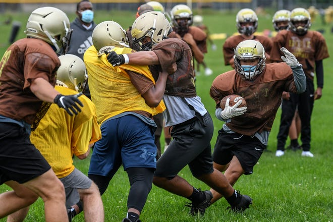 Holt's Malachi Davis, center, blocks for running back Marc Ward, right, during the Rams football practice on Wednesday, Sept. 9, 2020, at Holt High School.