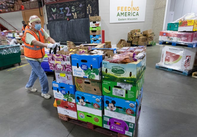 Volunteer Lane Kistlers moves items to a cooler at  Feeding America Eastern Wisconsin, 1700 West Fond du Lac Ave., in Milwaukee on Wednesday, September 9, 2020.