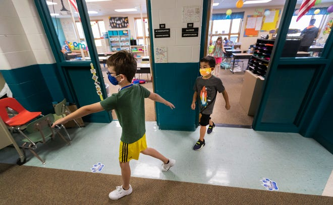 Second grade students at Lake Country School in Hartland place their arms out to maintain proper social distancing while heading outside for recess on Sept. 4, 2020. The school is maintaining its COVID-19 health measures through the end of the school year.