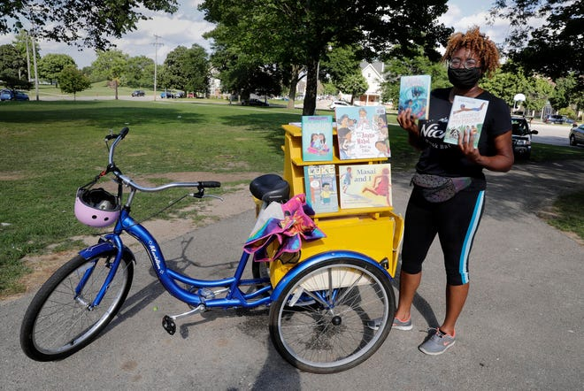 Cetonia Weston-Roy gathers books she reads to children at Carver Park. She aspires to open the first brick-and-mortar Black-owned bookstore in Wisconsin since the last one closed in 2017. Right now her bookstore, Niche Book Bar, exists as a tricycle with a bookshelf attached to the back of the bike.