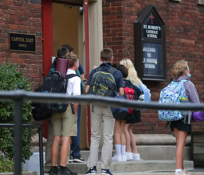 Children are seen arriving to start the day at St. Robert School in Shorewood in September. St. Robert's enrollment rose by about 50 students this year, most of those in families looking for in-person instruction for their children. The school announced that 63 students are quarantined after a teacher tested positive for COVID-19 in recent days.