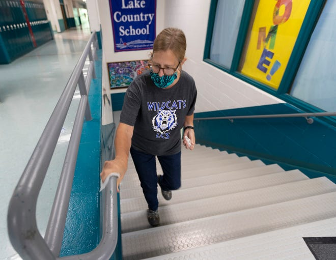 Librarian Linda Jensen cleans railings on Friday, Sept. 4, 2020, at Lake Country School in Hartland. Schools have been requiring masks throughout the school year to stop the spread of COVID-19, and are still requiring them even though the state mask mandate was overturned by the state Supreme Court earlier this week.