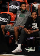 The Bucks' Giannis Antetokounmpo sits next to Sterling Brown on the bench.