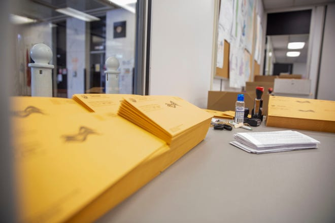 Envelopes for absentee ballots for voters to return by mail are marked with postage before being stuffed with the required election material before the 2020 election.