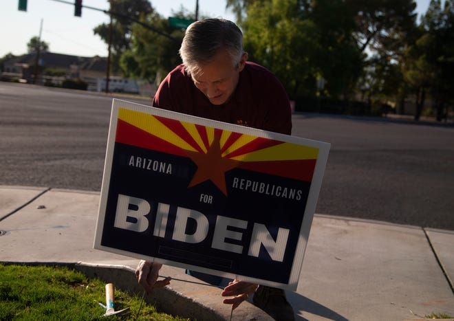 Un hombre coloca un cartel de Joe Biden en el cesped.
