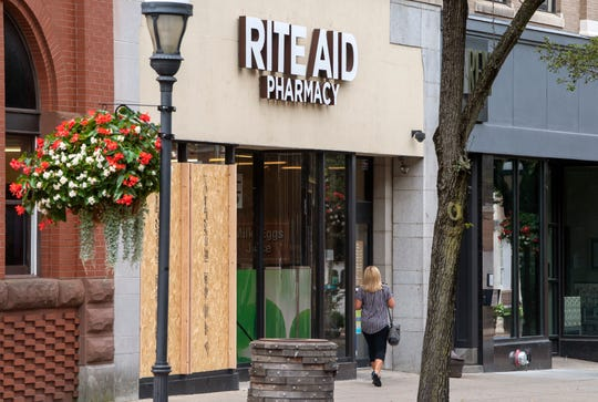 The Rite Aid in York with wood over two broken windows smashed by a man using a skateboard after he ransacked the inside of the store and attacking a shift manager.