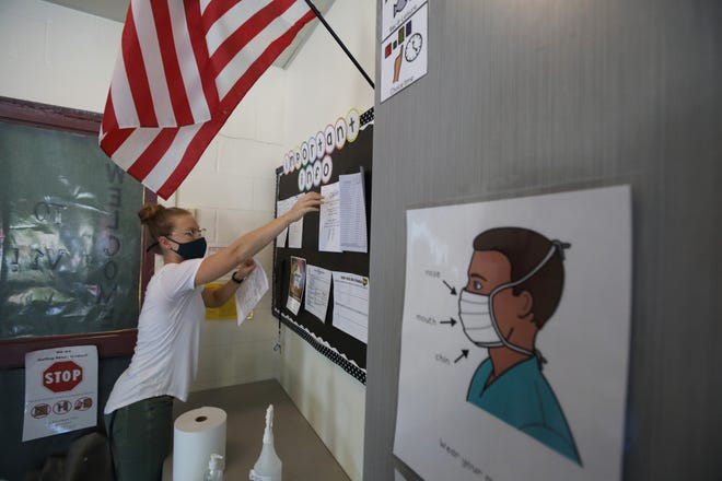 Teacher Emily Shaw sets up a bulletin board in her transition classroom at Creekside School in Fairport Wednesday, Sept. 9, 2020. The classroom has visual signs everywhere reminding students to wear a mask, and social distance.