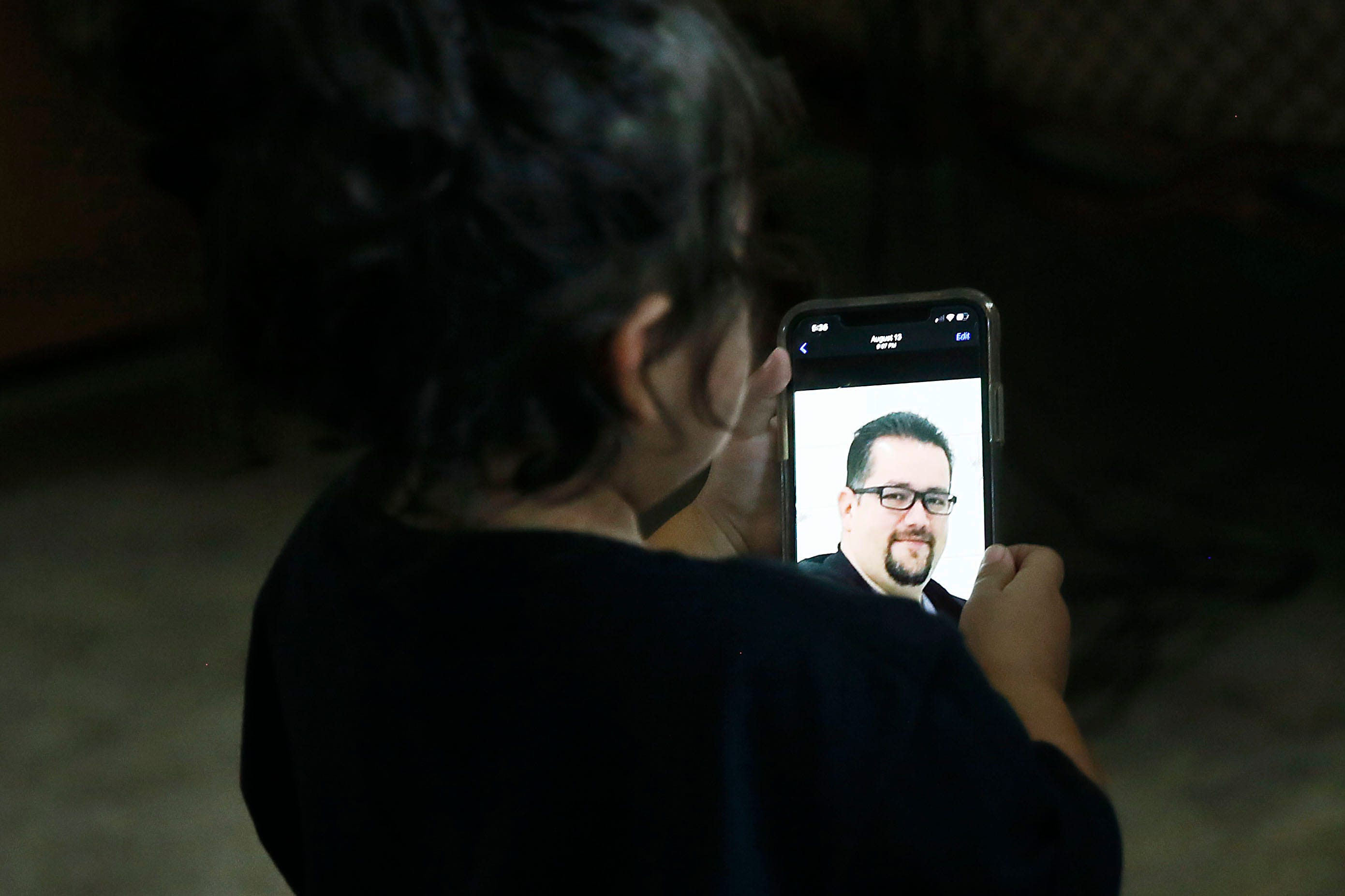 Desiree Morales looks at a photo of her dad, Daniel Morales, on her mom's phone. The El Paso nurse died of the coronavirus on Aug. 4.