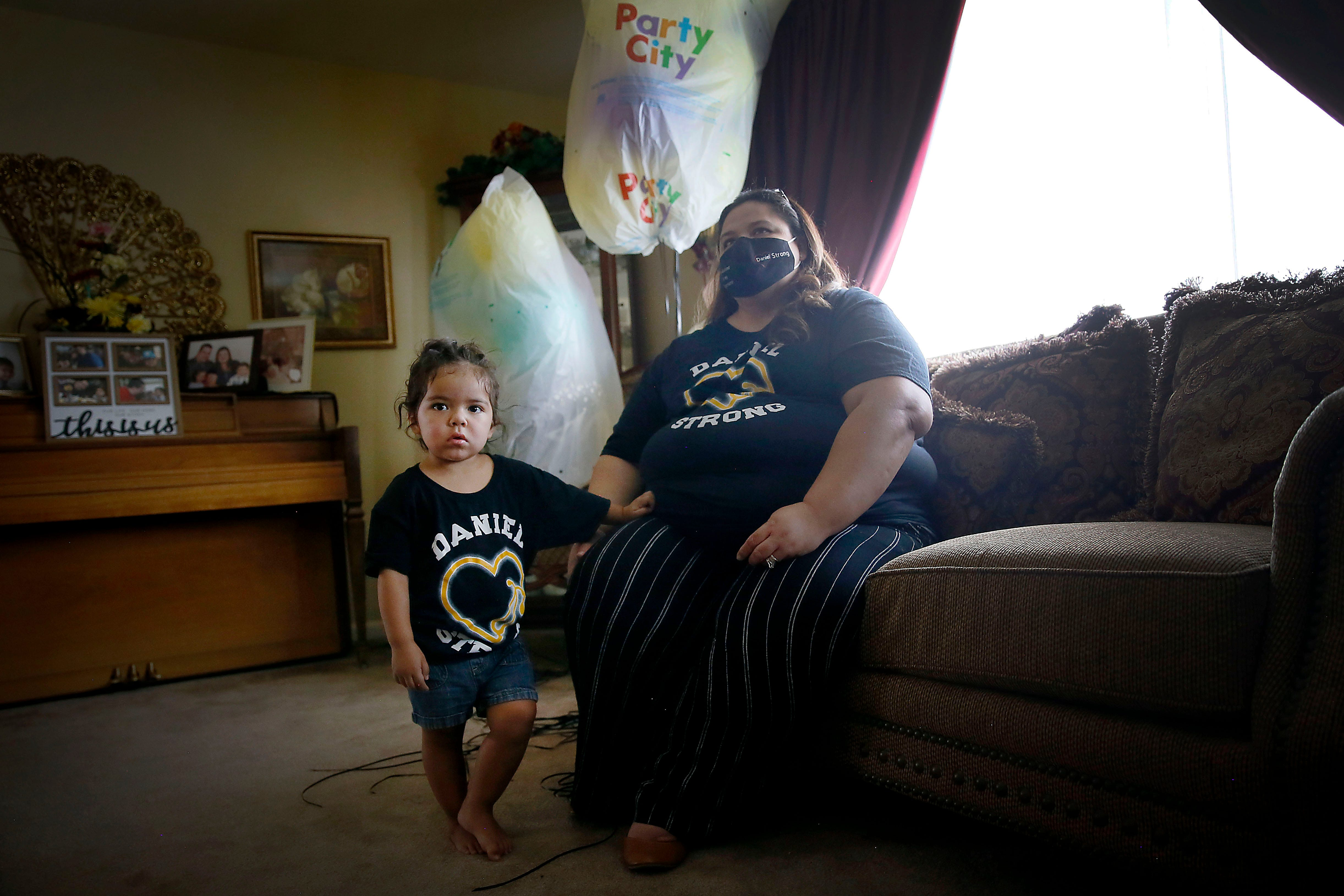 Erika Castor-Morales talks about her late husband, Daniel Morales, while holding her daughter, Desiree Morales, among balloons for what would have been his 40th birthday Aug. 21, 2020 at her in-laws' home in El Paso.