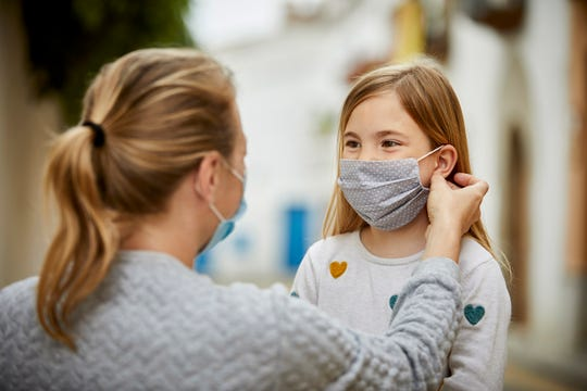 A mother helps her daughter put on a homemade face mask.