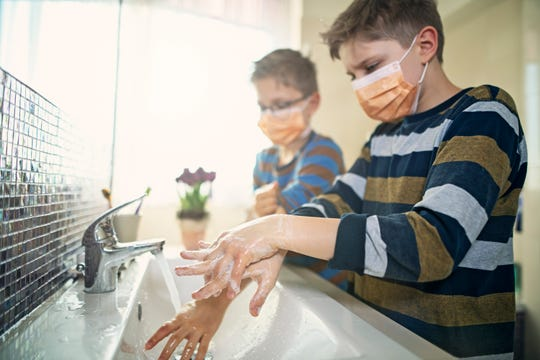 Two boys wash their hands while wearing face masks.