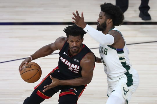 Forward Jimmy Butler, left, driving against Bucks guard Wesley Matthews, led the Heat with 17 points, 10 rebounds and six assists.