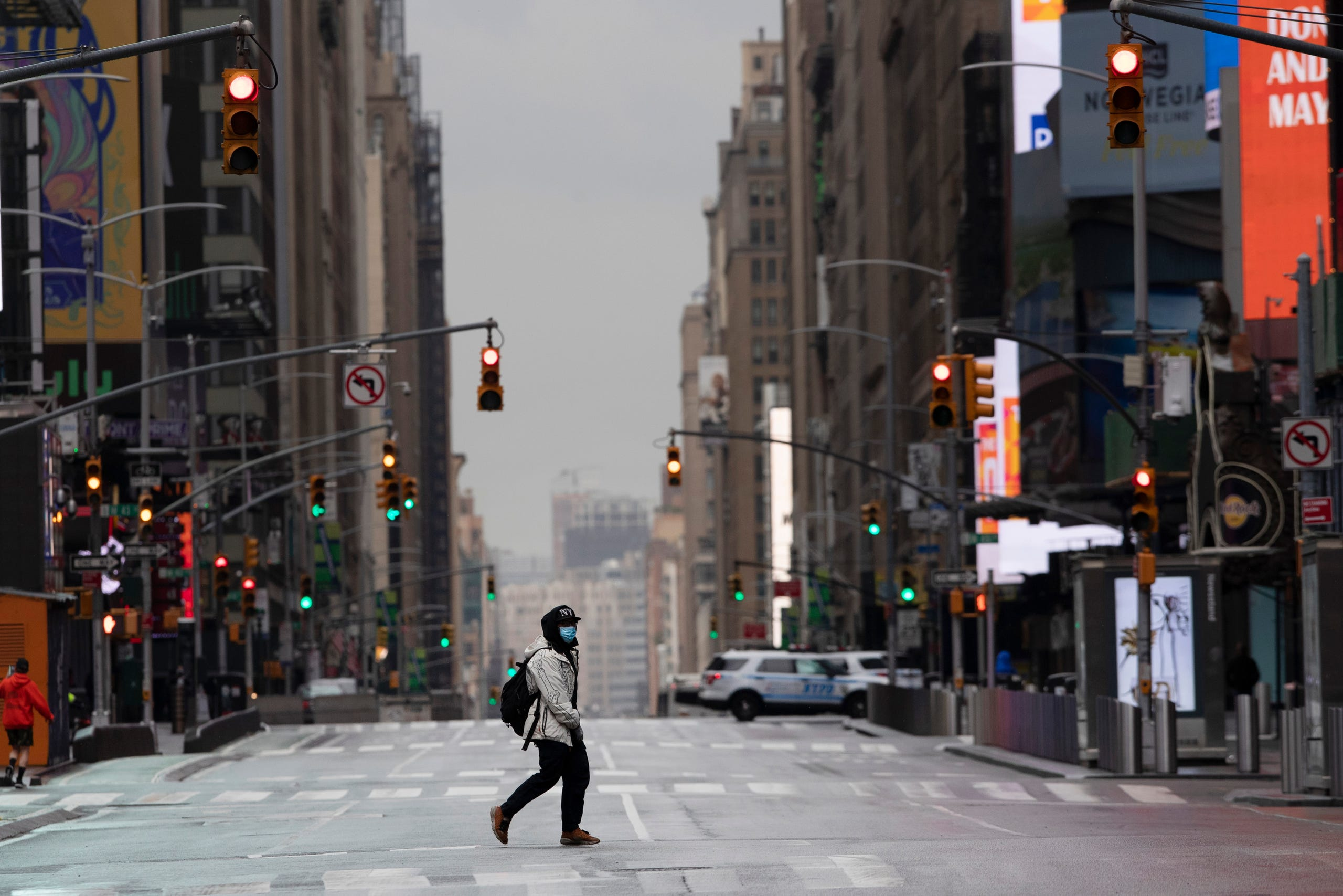 A man wearing a mask crosses the street in a quiet Times Square, Thursday, April 9, 2020, during the coronavirus epidemic in New York City.