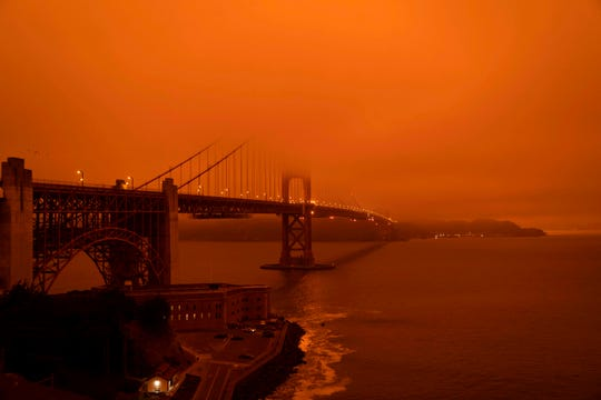 Cars drive along the Golden Gate Bridge under an orange, smoke-filled sky in San Francisco on Sept. 9.
