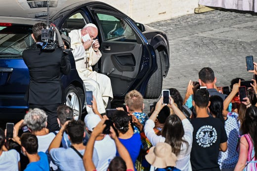 Pope Francis takes off his face mask as he arrives by car to hold a limited public audience at the San Damaso courtyard in The Vatican on September 9, 2020 during the COVID-19 infection, caused by the novel coronavirus.