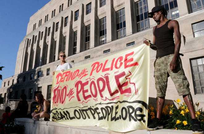 Protesters hold a banner calling for the defunding of police July 10, 2020, in Sheboygan, Wis.