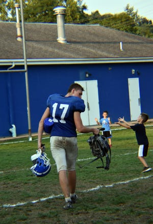 Sophomore wide receiver Brighton Mariacher (17) heads to the field house after Wednesday practice at Helling Stadium as the coach's children play catch in the background. Ellwood City's season home opener is at 7 p.m. Friday against the Mohawk Warriors.