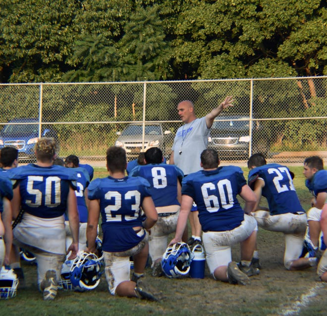 Ellwood City head coach Joe Lamenza discusses Wolverine football traditions with his team after Wednesday evening practice. Lamenza, a native of Ellwood City, is bringing back several traditions this season, such as the team's post-game salute to the marching band. Friday night's season opener has Ellwood City hosting the Mohawk Warriors at 7 p.m. at Helling Stadium.