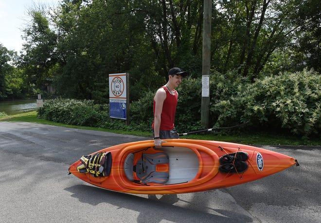 Kris Terrazzano, 25, carries his kayak after an afternoon on Little Beaver Creek at Lock 57 Community Park in Ohioville.