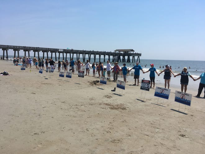 "Participants in ""Hands Across the Sand"" join hands on Tybee Island in May 2019 in a show of solidarity against offshore drilling and seismic testing."