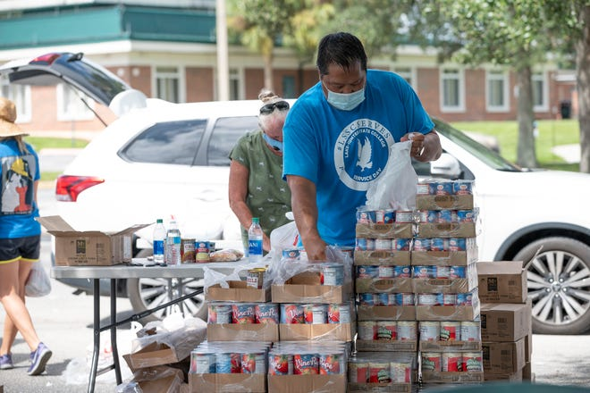 Volunteers fill bags of groceries to be distributed at a Second Harvest food drop at Lake-Sumter State College in Clermont on Thursday.