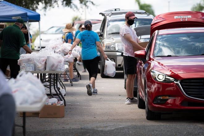 Volunteers load cars full of groceries at a Second Harvest food drop at Lake-Sumter State College in Clermont on Thursday. [Cindy Peterson/Correspondent]