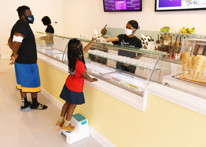 Danielle McQueen, owner of Springfield Scoops, serves Nyvae Arnold, 5, at the newly opened ice cream and frozen yogurt shop on Wednesday.