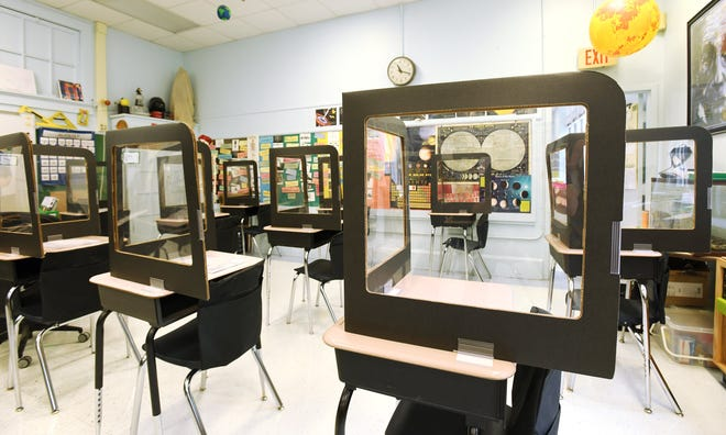 Desks inside a fifth-grade classroom at Fishweir Elementary School have cardboard and clear plastic shields to help prevent the spread of the coronavirus between students.