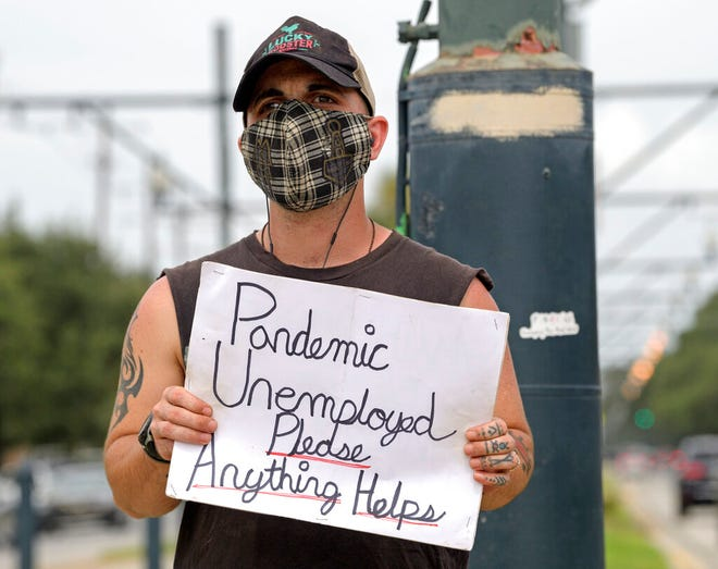 Sean Harris holds a sign asking for help while standing on the neutral ground on Carrollton Ave. at Bienville Ave. in New Orleans, Sept. 4. Harris had just completed training to be a hunted history tour guide in the French Quarter when the coronavirus pandemic hit. He has not been able to find a job since.