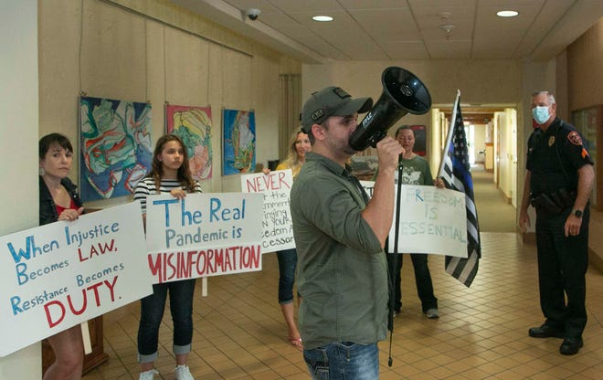 A Lakeland resident and anti-mask protester, who would only identify himself as Nick, leads a group of demonstrators inside the lobby of Lakeland City Hall on Tuesday as city commissioners voted in a virtual session to extend the city's face mask mandate until Oct. 5.