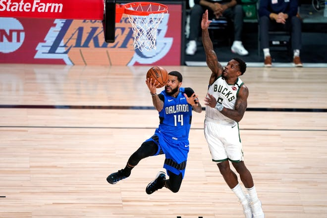 Orlando Magic's D.J. Augustin (14) goes up for a shot as Milwaukee Bucks' Eric Bledsoe (6) defends during the first half of their first-round NBA playoff game on Aug. 29.
