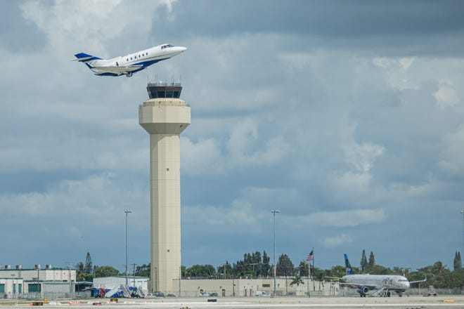 A small plane takes off past the control tower at Palm Beach International Airport, Wednesday, September 9, 2020.