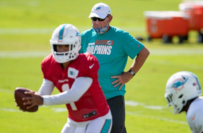 Dolphins offensive coordinator Chan Gailey watches rookie quarterback Tua Tagovailoa during practice.
