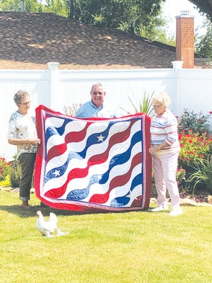 Karen Pinkle (right) presents Prattan Merle Rose and his wife Beth Rose with a Quilt of Valor, made by the local branch of the Quilts of Valor. Rose served in the United States Army from 1961-63.
