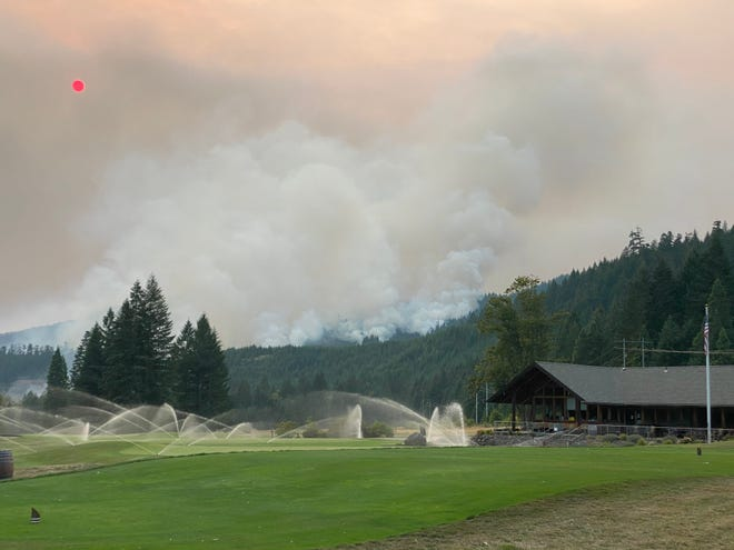 The Holiday Farm Fire is seen behind Tokatee Golf Club on Thursday morning as sprinklers run to try and protect the golf course from the growing fire. [Contributed photo]