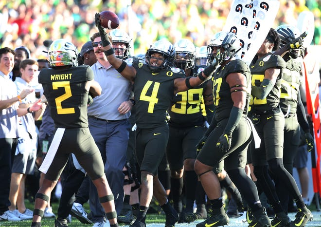 Oregon's Thomas Graham Jr. (4) celebrates with teammates after making an interception during the second quarter of the Rose Bowl win against Wisconsin. (Chris Pietsch/The Register-Guard)
