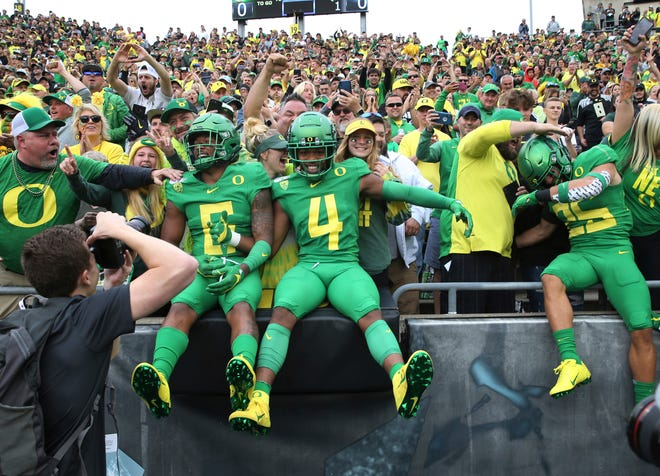 Oregon's Deommodore Lenoir, left, Thomas Graham Jr. (4) and Brady Breeze leap into the stands with Duck fans before a Sept. 7, 2019, game against Nevada at Autzen Stadium. The Ducks have lost Lenoir and Graham on back-to-back after they chose to bypass their senior seasons. (Chris Pietsch/The Register-Guard)
