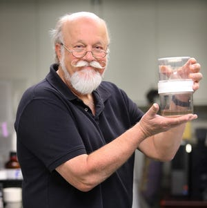 Paul Linser holds a mosquito culture vessel.
