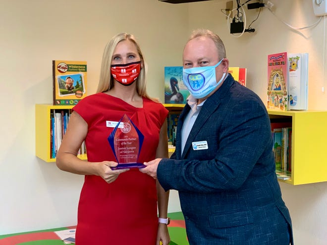 Child Protection Center Executive Director Doug Staley presents the Community Partner of the Year award to Melissa Hembree, president of the Junior League of Sarasota.