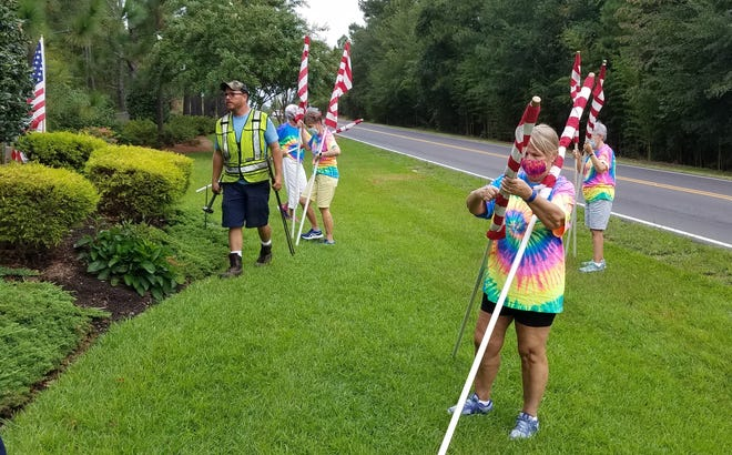 Members of the Loblolly Garden Club of Pinehurst place flags Thursday in honor of the anniversary of the 9/11 terrorist attacks.