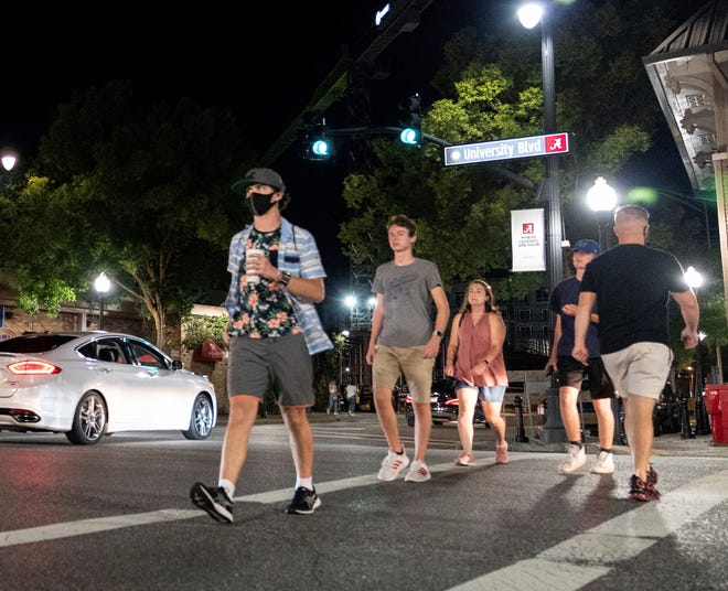 People make their way along The Strip, the University of Alabama's bar scene, on Aug. 15 in Tuscaloosa. Three weeks into the fall semester, the school is enforcing new COVID-19 regulations amid high positive test counts.
